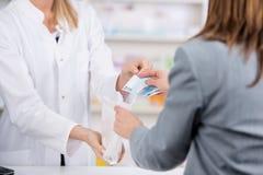 O paciente paga pela medicina ao farmacêutico fotos de stock royalty free