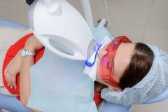 O paciente submete-se a um procedimento para os dentes que clarea com uma lâmpada ultravioleta fotografia de stock