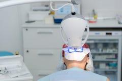 O paciente submete-se a um procedimento para os dentes que clarea com uma lâmpada ultravioleta imagens de stock