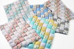 O pacote de cobertores patchworked coloridos com unicórnio e as estrelas projetam no fundo branco - seis partes Fotografia de Stock