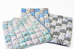 O pacote de cobertores patchworked coloridos com unicórnio e as estrelas projetam no fundo branco - três partes Imagens de Stock