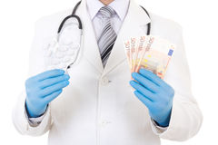 O pacote dos comprimidos e de euro- cédulas nas mãos do doutor isolou o Foto de Stock Royalty Free