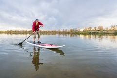 O paddler masculino levanta-se sobre o paddleboard Imagens de Stock