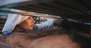 O padeiro bonito da senhora em um uniforme à moda em uma cozinha da padaria pôs em ordem o pão cozido fresco depois que toma algu vídeos de arquivo