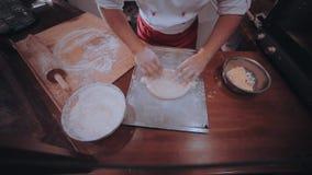 O padeiro desenrola a massa em uma mesa de cozinha de madeira polvilhada com a farinha filme