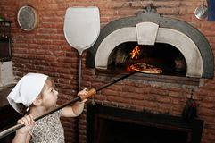 O padeiro do bebê remove a pizza do fogão dequeimadura Fotografia de Stock