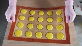 O padeiro está cozinhando bolinhos de amêndoa na esteira do silicone do estêncil na tabela, preparando-se para a massa de cozimen filme