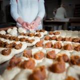O padeiro faz bolos com enchimento do doce e do leite condensado da massa fotografia de stock
