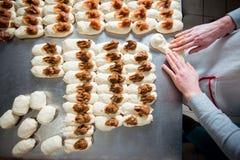 O padeiro faz bolos com enchimento do doce e do leite condensado da massa fotos de stock royalty free