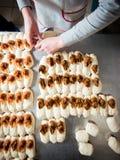 O padeiro faz bolos com enchimento do doce e do leite condensado da massa fotografia de stock royalty free