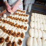 O padeiro faz bolos da massa com enchimento do leite condensado imagem de stock