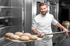 O padeiro que toma para fora do forno cozeu o pão do buckweat Fotografia de Stock