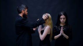 O padre abençoa duas meninas em um fundo preto O conceito da adoração Duas meninas vestidas no preto são confessadas a filme