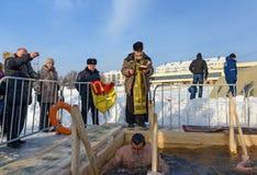 O padre consagra o furo do gelo no dia do esmagamento Rússia Fotos de Stock