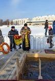 O padre consagra o furo do gelo no dia do esmagamento Rússia Imagem de Stock