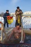 O padre consagra o furo do gelo no dia do esmagamento Rússia Fotografia de Stock