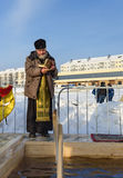 O padre consagra o furo do gelo no dia do esmagamento Rússia Imagens de Stock