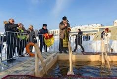 O padre consagra o furo do gelo no dia do esmagamento Rússia Foto de Stock