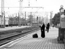 O padre espera um trem Fotos de Stock Royalty Free