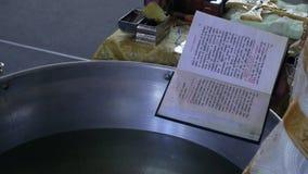 O padre lê a oração perto da bacia do batismo vídeos de arquivo