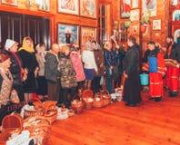 O padre ortodoxo consagra a água santamente com bolos e ovos da Páscoa em uma igreja de madeira Fotografia de Stock Royalty Free