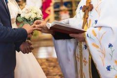 O padre puxa a aliança de casamento para o noivo imagens de stock