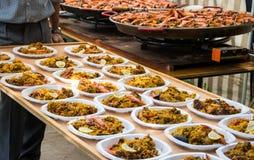O paella pronto espalhou para fora em placas plásticas para a distribuição em uma tabela comum imagens de stock