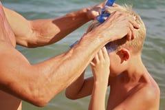 O pai ajuda o filho a pôr mergulhar a máscara Menino e homem na praia na frente do mar Férias ativas das férias de verão Fotos de Stock Royalty Free