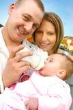 O pai alimenta o leite ao bebê Imagens de Stock Royalty Free