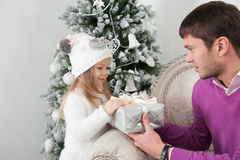 O pai apresenta a presente sua filha no tempo do Natal Foto de Stock