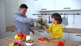 O pai atrativo e o filho muito bonito estão tendo o divertimento em casa na cozinha Lento-movimento Pai e filho feliz que têm o d filme