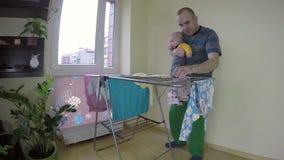 O pai com o bebê em suas mãos pegara a lavanderia seca 4K vídeos de arquivo