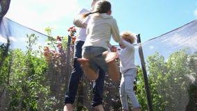 O pai com filho tem o divertimento no trampolim Tiro do movimento lento vídeos de arquivo