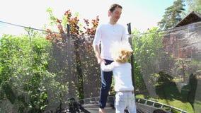 O pai com filho tem o divertimento no trampolim Tiro Handheld video estoque