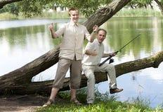 O pai com o filho na pesca, mostras o tamanho dos peixes Imagem de Stock