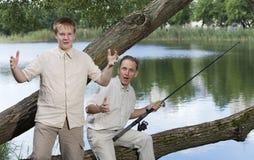 O pai com o filho na pesca, mostras o tamanho dos peixes Imagens de Stock