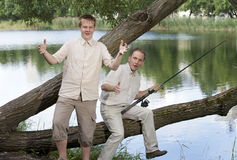 O pai com o filho na pesca, mostras o tamanho dos peixes Fotografia de Stock Royalty Free
