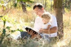 O pai com sua filha pequena lê a Bíblia Imagem de Stock Royalty Free