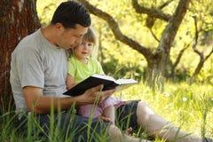O pai com sua filha pequena lê a Bíblia Fotografia de Stock Royalty Free