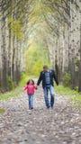 O pai corre com uma filha e guarda sua mão na natureza em férias do dia do outono Paizinho e menina que andam e que jogam no parq imagem de stock