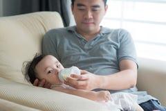 O pai dá mamadeira o leite ao bebê imagem de stock