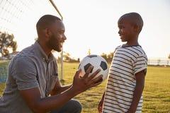 O pai dá uma bola a seu filho durante um jogo de futebol foto de stock