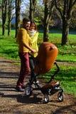 O pai da mulher e do homem empurra o carrinho de criança de bebê ao andar através do parque do outono, ligação de família Ligação imagens de stock