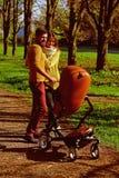 O pai da mulher e do homem empurra o carrinho de criança de bebê ao andar através do parque do outono, ligação de família Ligação imagens de stock royalty free
