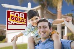 O pai da raça misturada, reboque do filho, parte dianteira da casa, vendeu o sinal Imagens de Stock