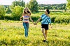 O pai e o adolescente, a mãe feliz e a filha adolescente 13, 14 anos de mãos velhas da posse vão conversa do riso foto de stock royalty free