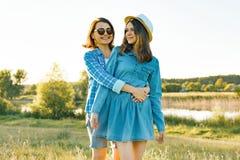 O pai e o adolescente, a mãe e a filha do adolescente de 14 anos abraçam o sorriso na natureza Por do sol do fundo, paisagens rús foto de stock royalty free