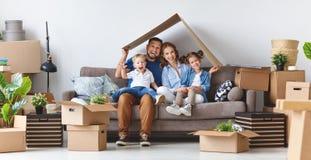 O pai e as crianças felizes da mãe da família transportam-se ao apartamento novo imagens de stock