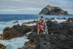 O pai e as crianças ficam perto da costa de mar em Garachico Imagens de Stock