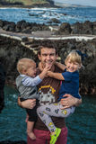 O pai e as crianças ficam perto da costa de mar em Garachico Imagem de Stock